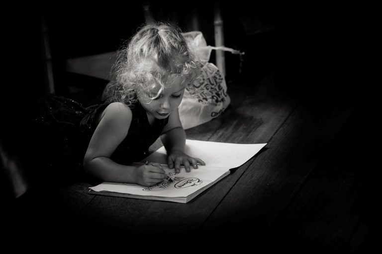 girl drawing underneath table at wedding