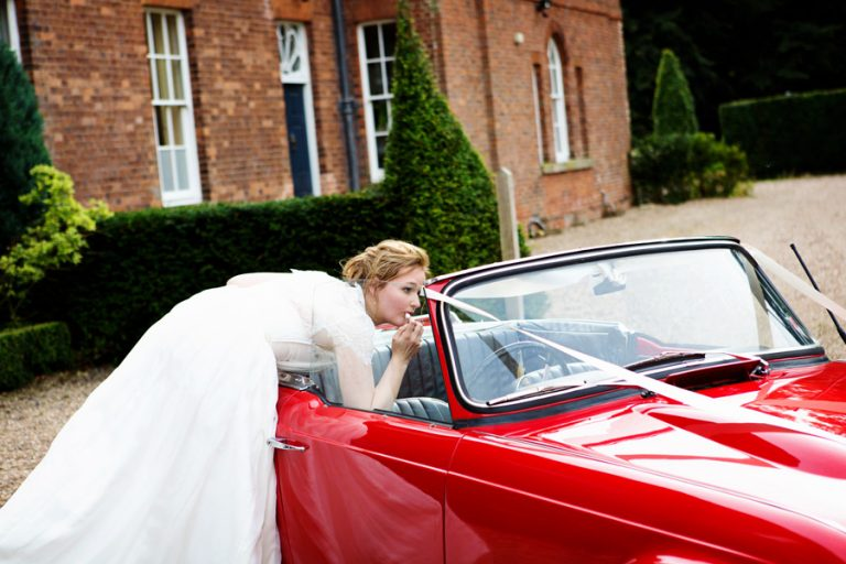 bride putting lipstick on in window of red sports car