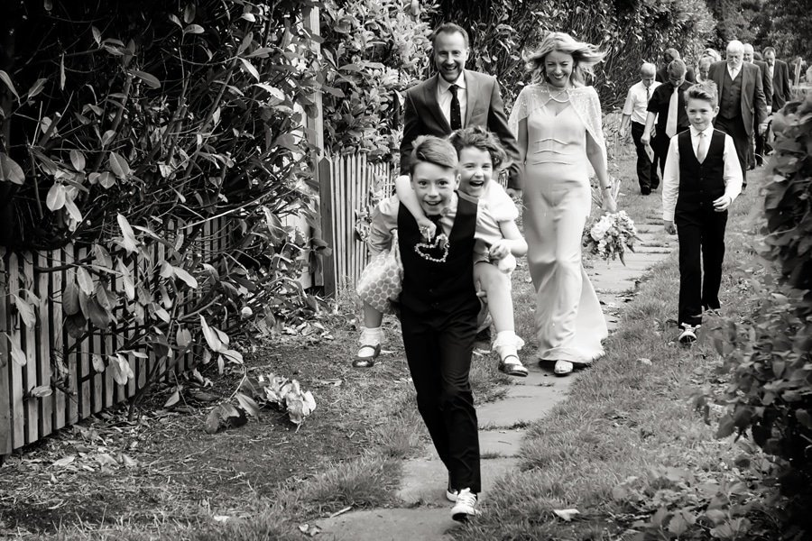bride and groom walking with guest and children having piggy back