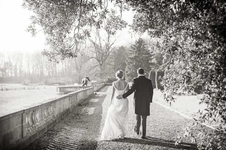 bride and groom walking away under trees at Prestwold Hall