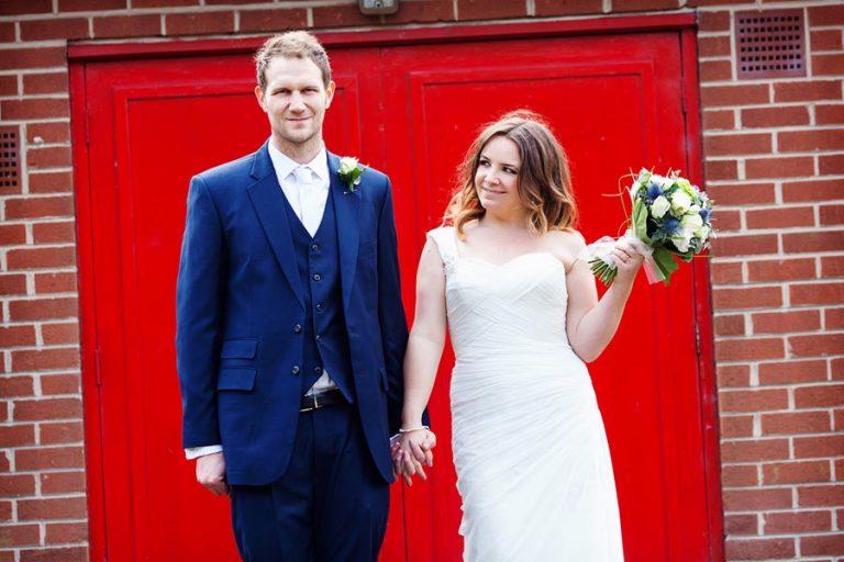 bride and groom in front of bright red door