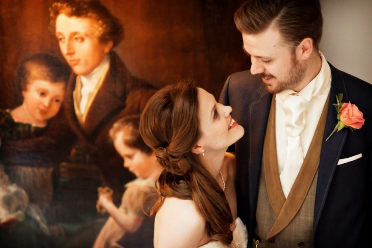 bride and groom in front of art painting at a norwood park