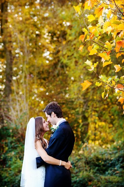 bride and groom in autumn leaves at norwood park