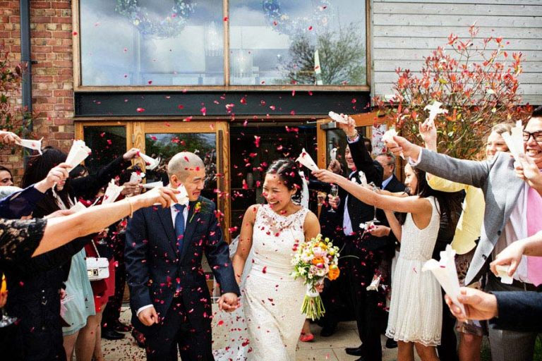 guests throwing confetti on bride and groom at Carriage Hall