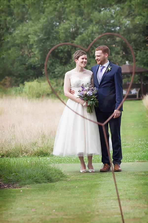 bride and groom framed by metal heart at Floral Media