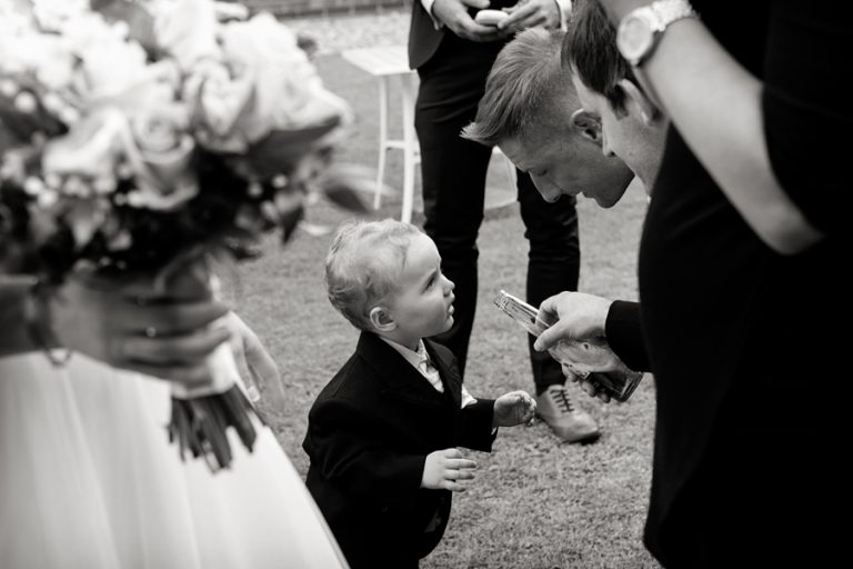 usher pretending to give boy a drink at wedding reception