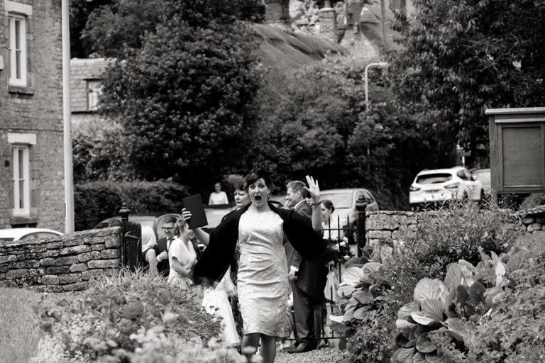 wedding guest laughing walking down to church
