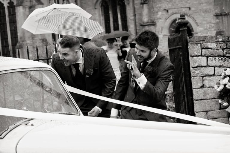wedding guests waiting at bride and groom in car