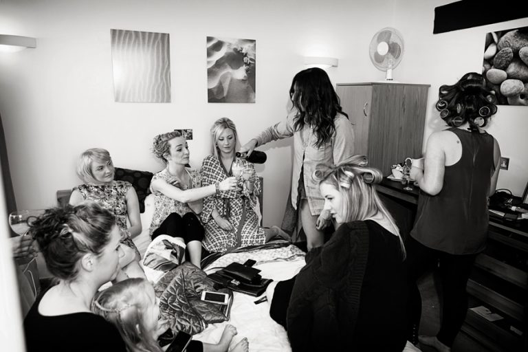 bride with lots of bridesmaids drinking whilst getting ready for wedding