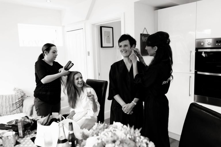 bride laughing whilst having her hair done with friends