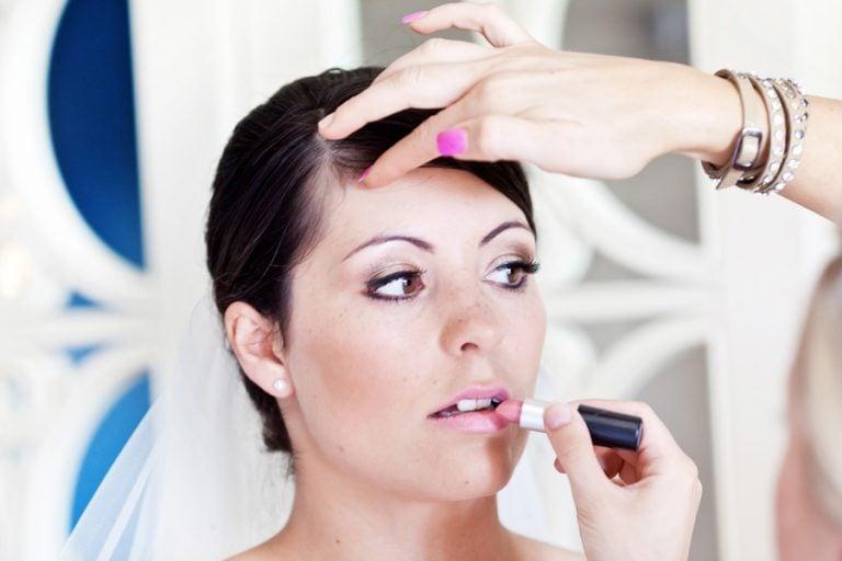 bride having pink lipstick put on