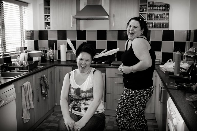 bride and sister laughing at bride's hair