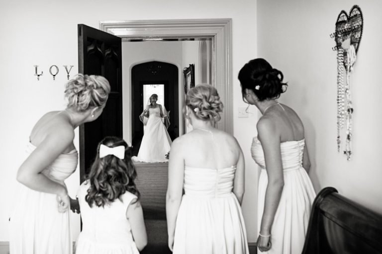 bridesmaids watching bride come out of bedroom in wedding dress
