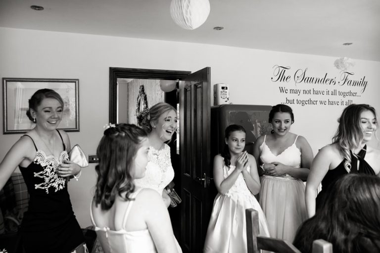 bride and bridesmaids laughing at home before leaving for church