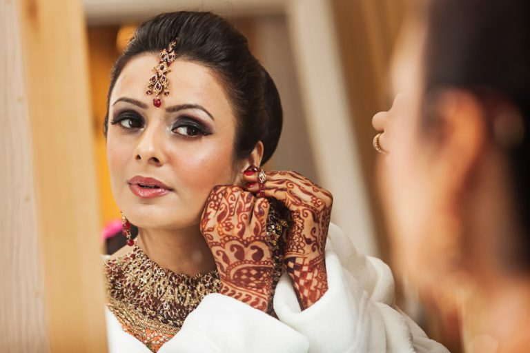 asian bride looking in mirror with henna on hats