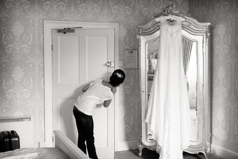 bride peaking around door with wedding dress hanging on wardrobe