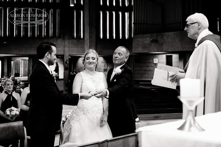 bride's dad handing over daughter's hand to groom in church