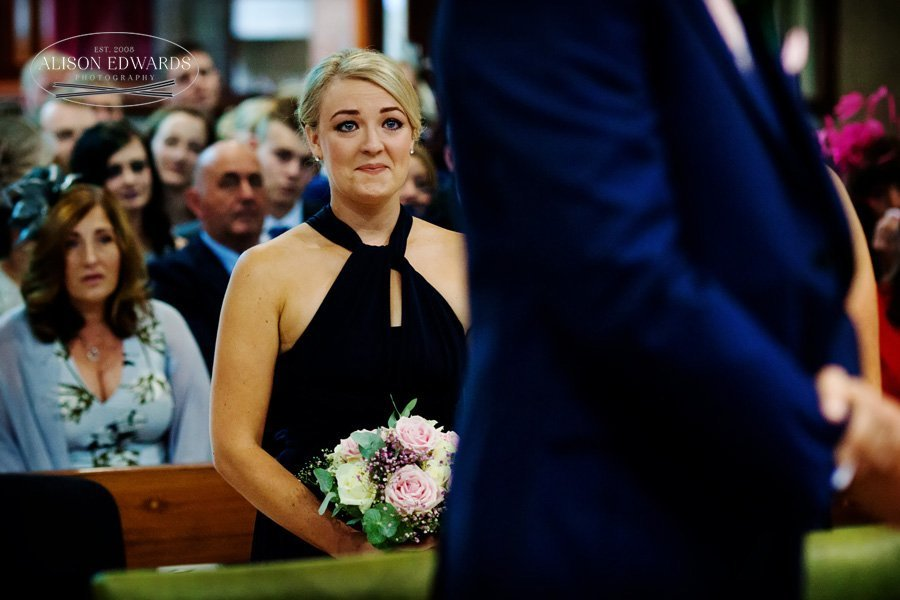 bridesmaid fighting back the tears during marriage ceremony