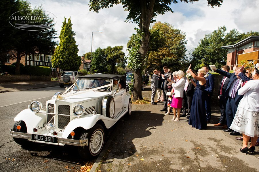 bride and groom leaving church in wedding car guests waving