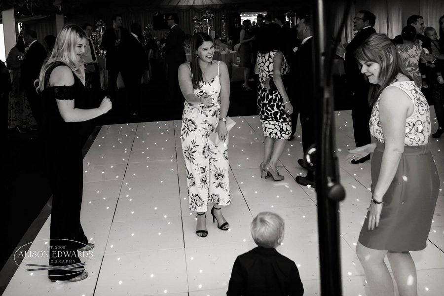 wedding guest pointing to child on dance floor