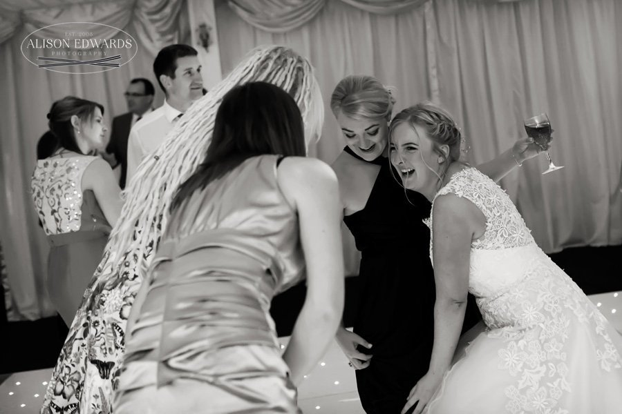 bride laughing and dancing with bridesmaids and friends