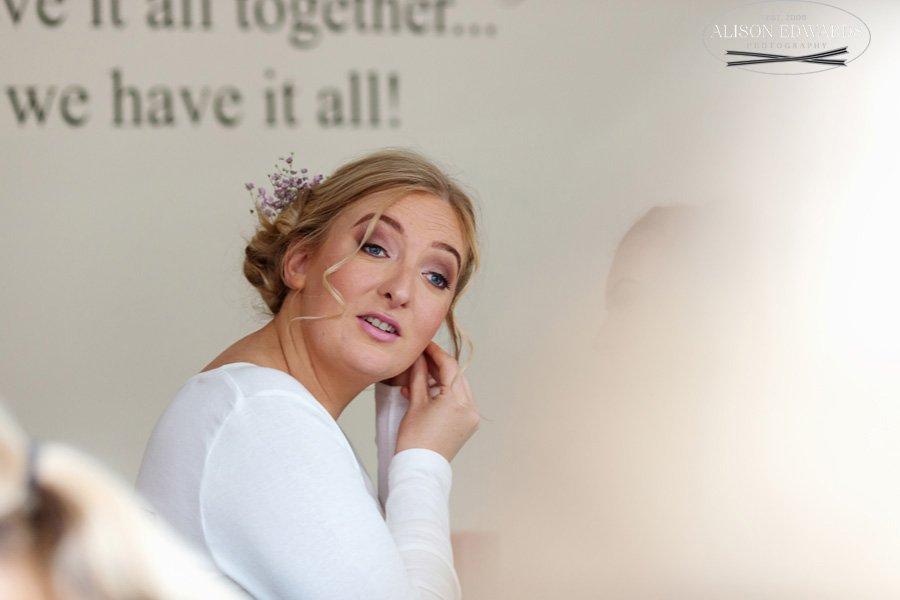 bride putting earrings in