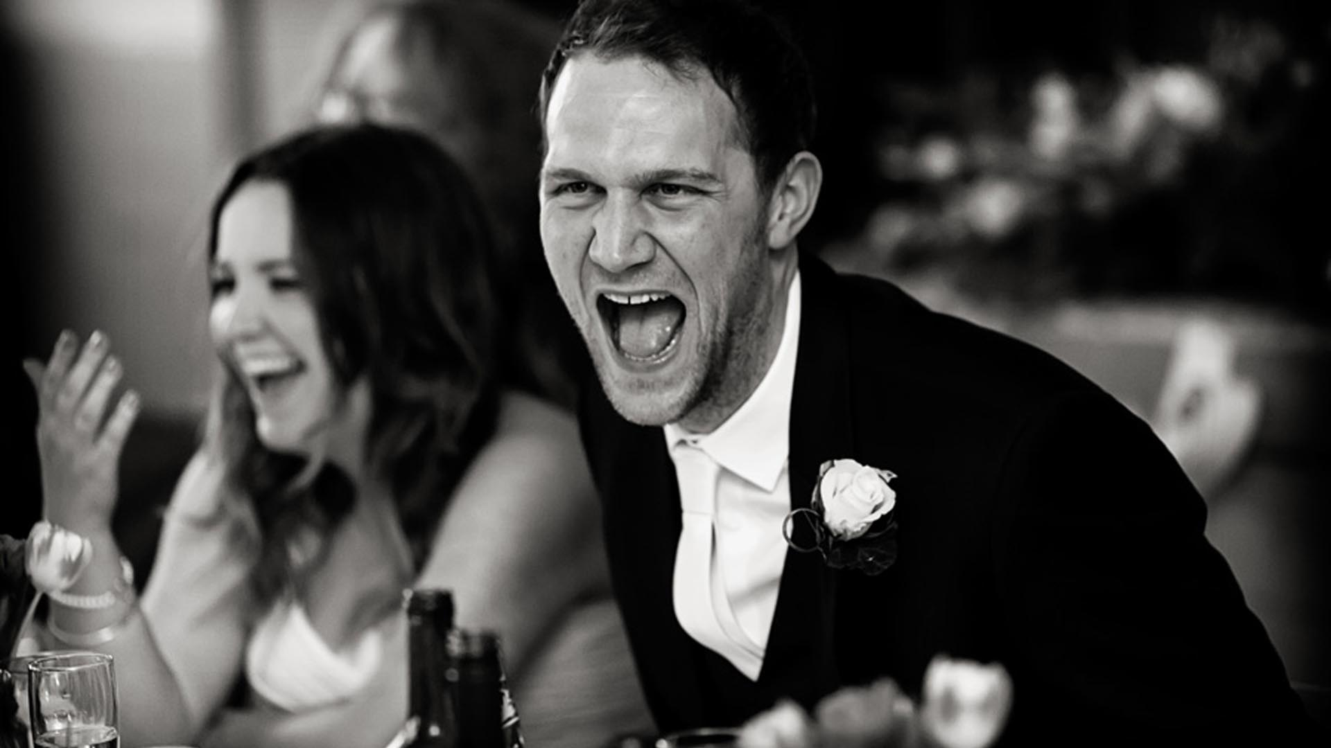 groom laughing out loud with bride at wedding speeches