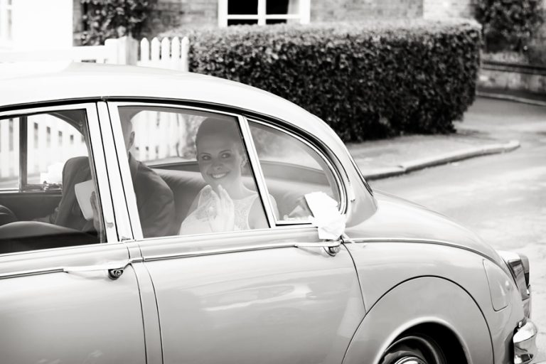 bride arriving at church in old car