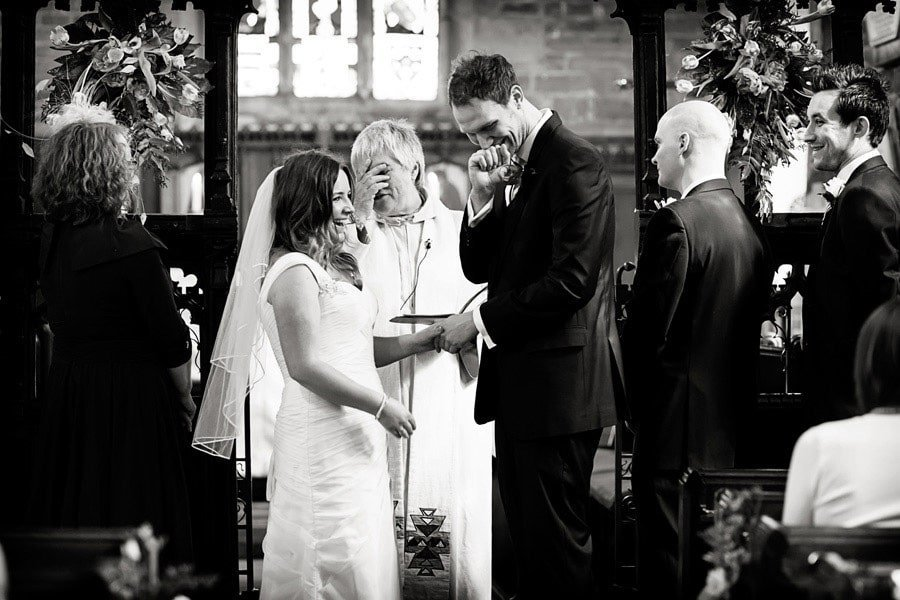 bride groom and vicar laughing in church during ceremony
