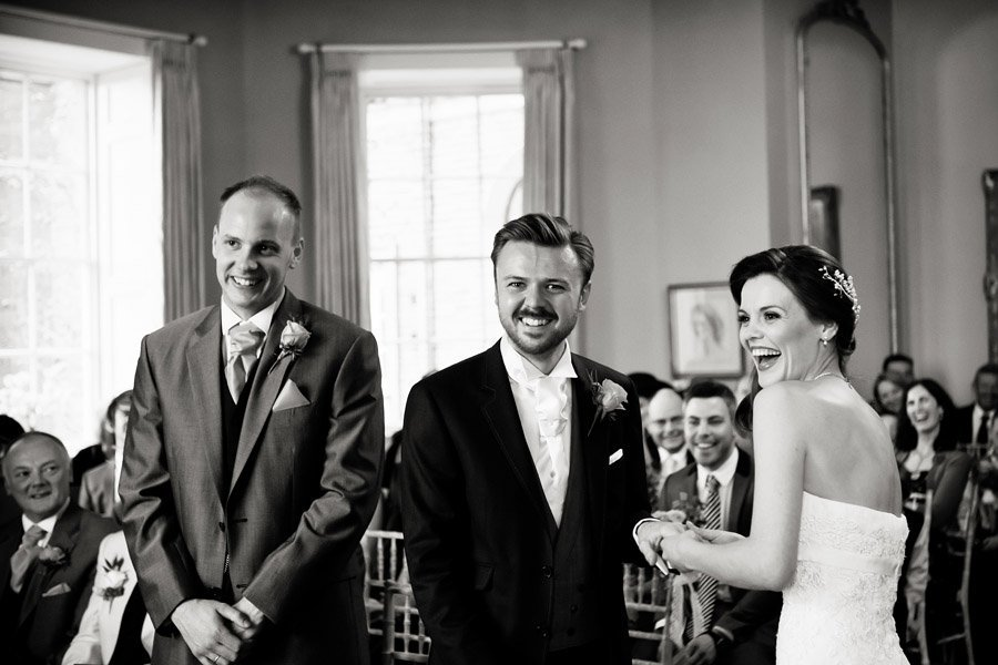 bride and groom laughing putting rings on