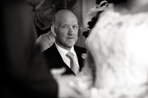 bride's dad looking at bride and groom during wedding vows
