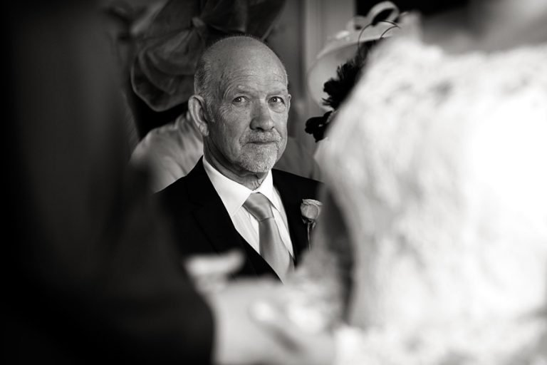 bride's dad looking at bride and groom during wedding vows captured by Nottingham wedding photographer