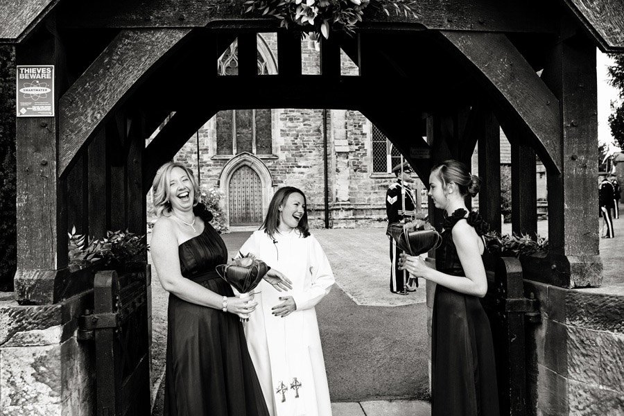 bridesmaids laughing with vicar outside church