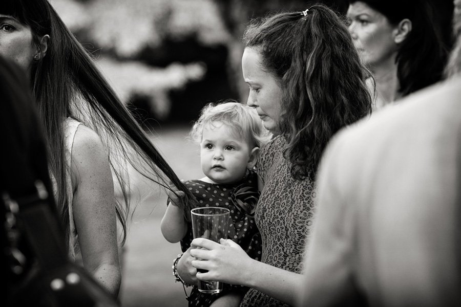 young girl pulling lady's hair at wedding drinks reception