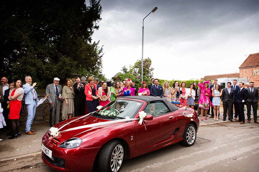 bride and groom driving away in red sports car with all guests waving