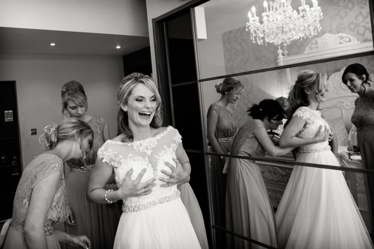 bride laughing being fastened into her dress captured by Nottingham wedding photographer