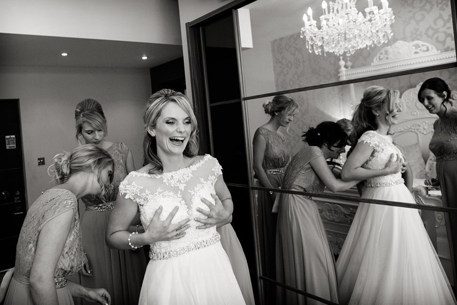 bride laughing being fastened into her dress