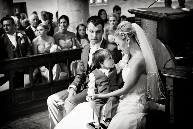 bride and groom with son at wedding alter looking lovingly at each other