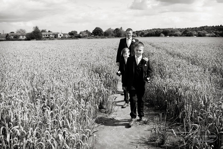 groom and sons walking across cornfield to church