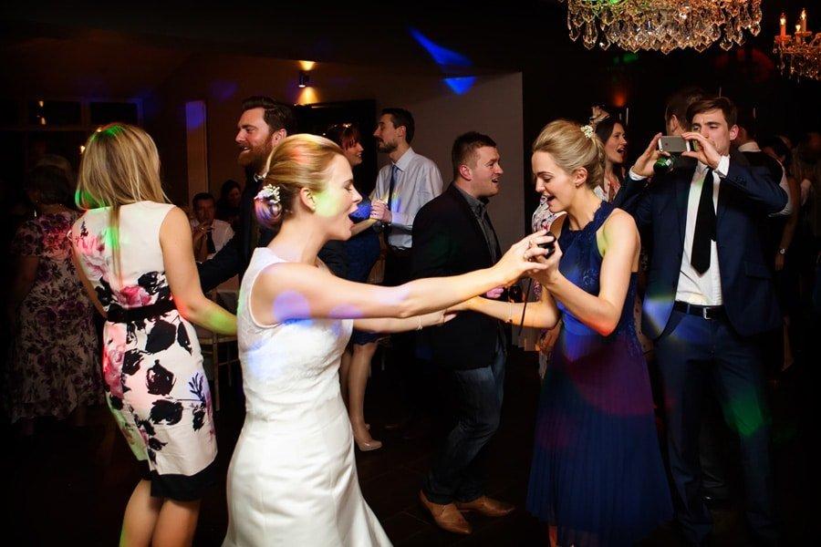 bride and bridesmaid dancing at old vicarage