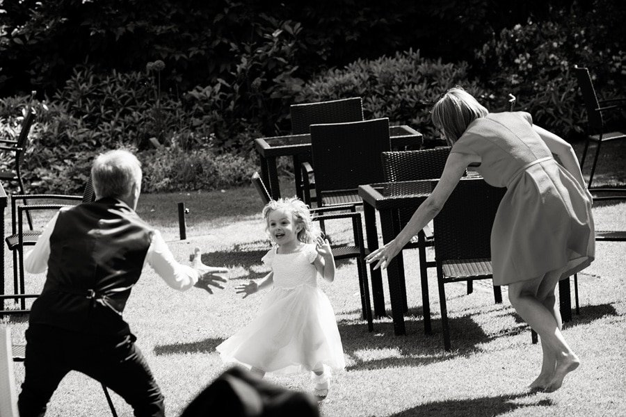 guests playing chase with child at wedding