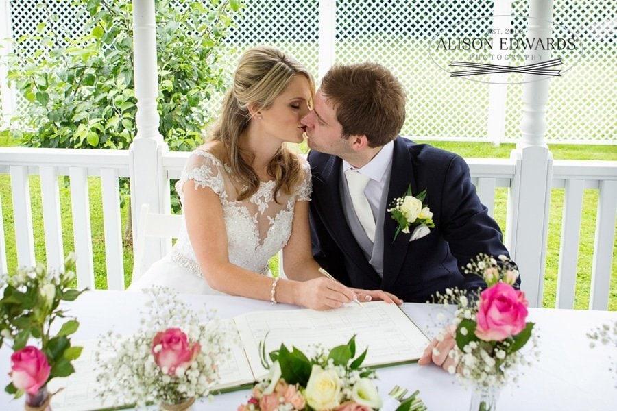 bride and groom kissing signing register in bandstand old vicarage
