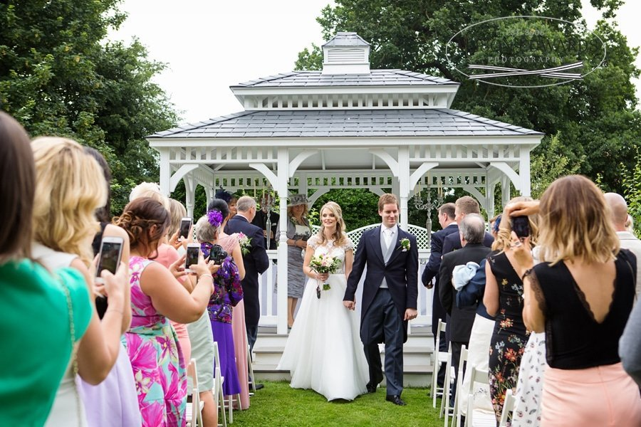 bride and groom walking down aisle old vicarage bandstand