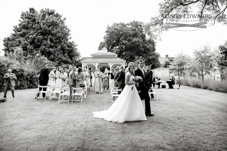 bride and groom walking down aisle bandstand in background