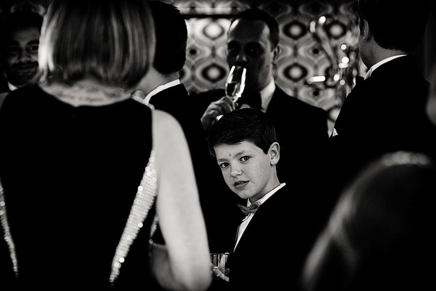 boy staring through wedding guests