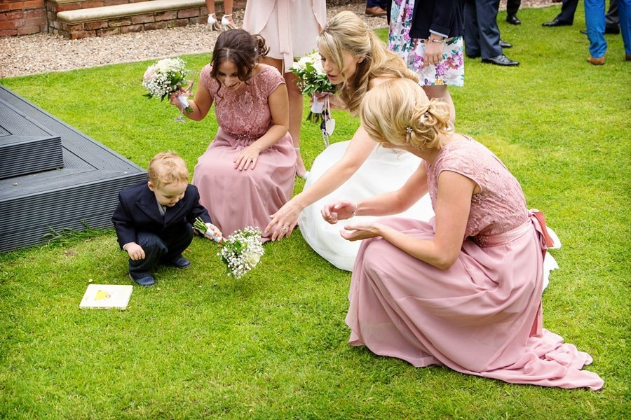 pageboy messing with bride's bouquet and bridesmaids stopping him