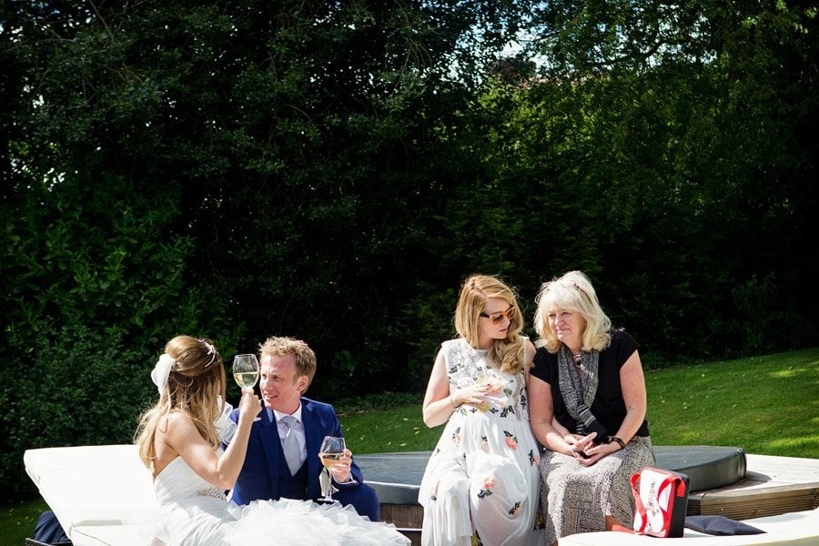 bride and groom and guests sitting talking in gardens old vicarage