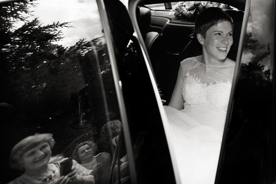 bride in wedding car with reflections of guests