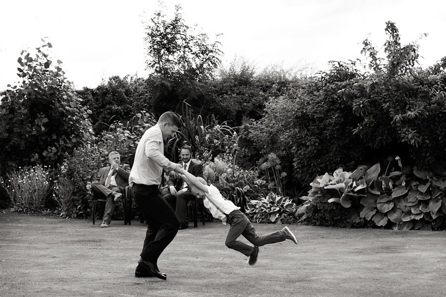 man swinging boy around in gardens at Floral Media wedding