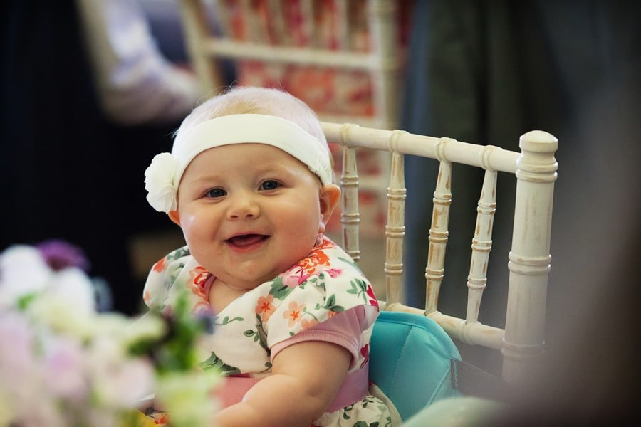baby smiling during dinner at Floral Media wedding